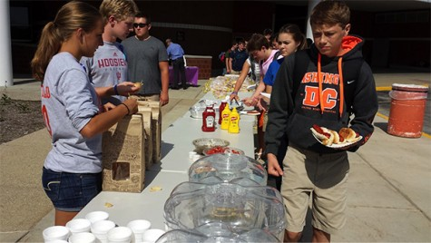Junior Kayla Gastineau serves chips from Chipolte during Thursday's cookout.