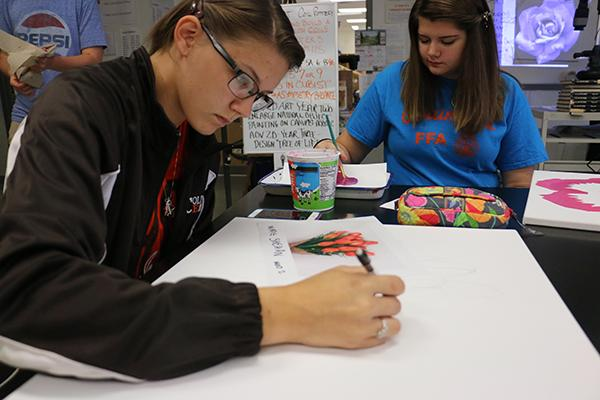 Juniors Madie Shehan (left) and Ashlyn Mills (right) work on projects during 2D art.