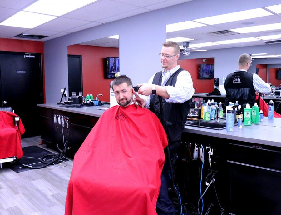 East graduate Clint Noble works in his barber shop located on Washington Street in Columbus.