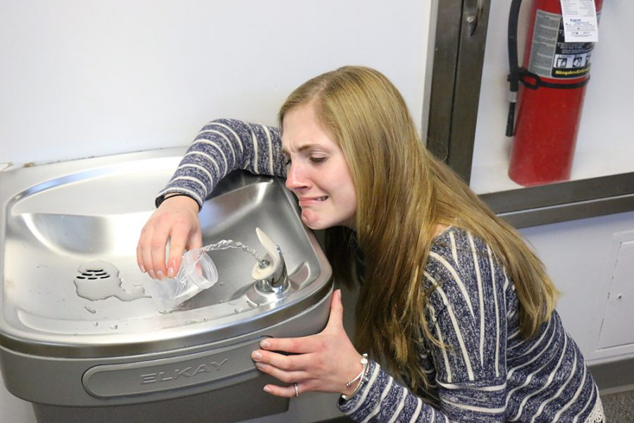 Natalie Glaid fills a sample cup with water from the third floor.