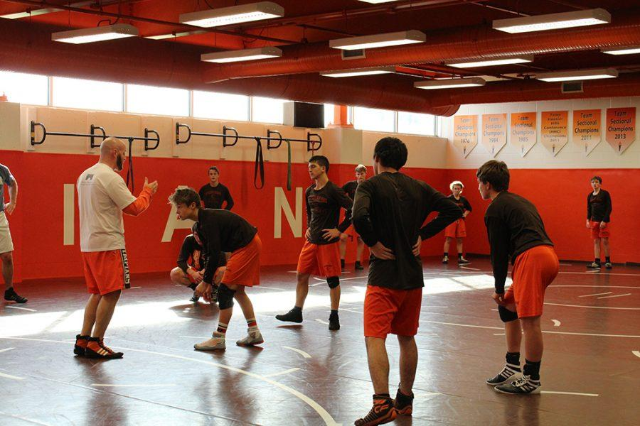 Coach Cooper gives a demonstration during wrestling practice.