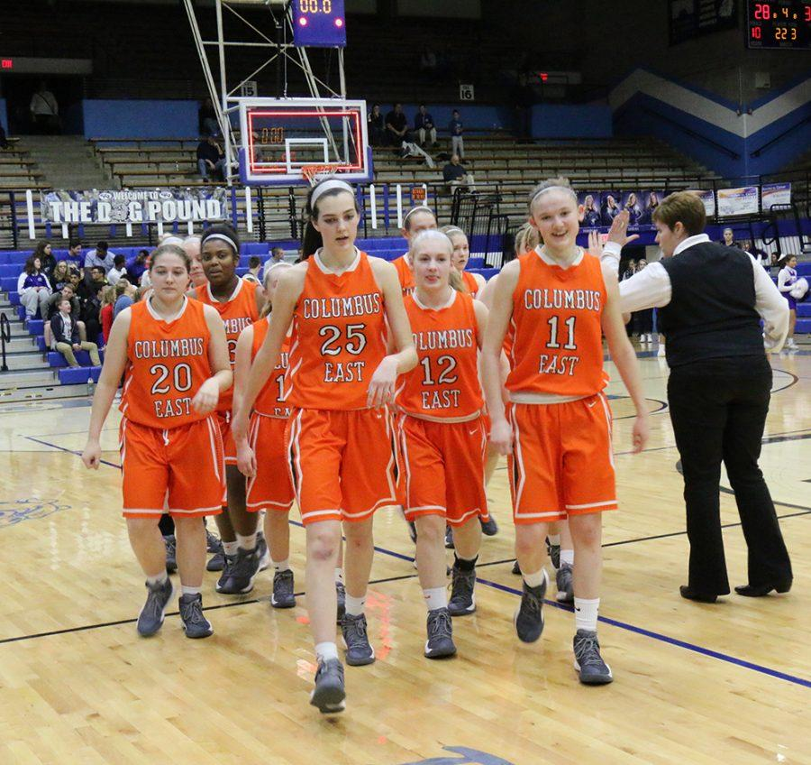 The Lady Olympians, led by Kristen Lyons and Britney Ballard, walk off the court after their warmup.