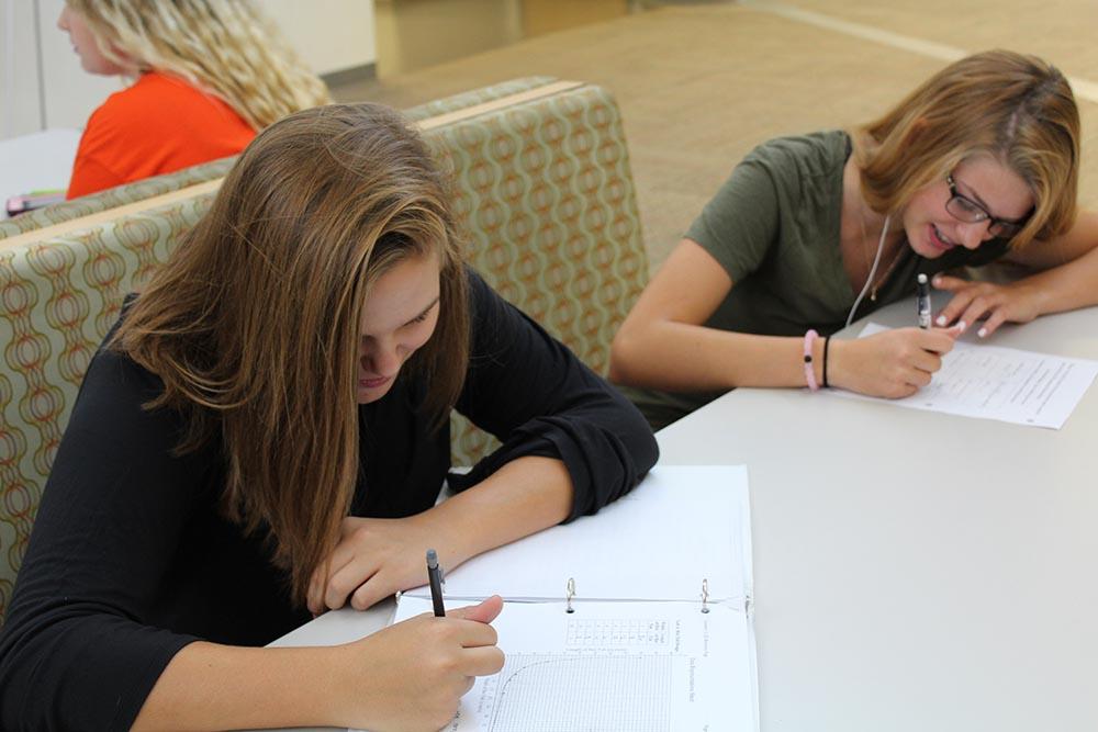 Freshmen Olivia Balser and Cassidy Schnur work on schoolwork in resource.