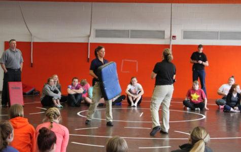 Officer Q leads senior girls through self defense workshop