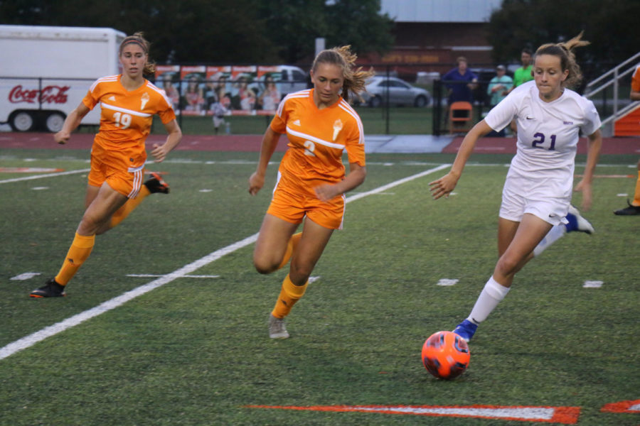 Senior Emily Stiles and freshman Norah Dwenger race to get the ball from Bloomington South.
