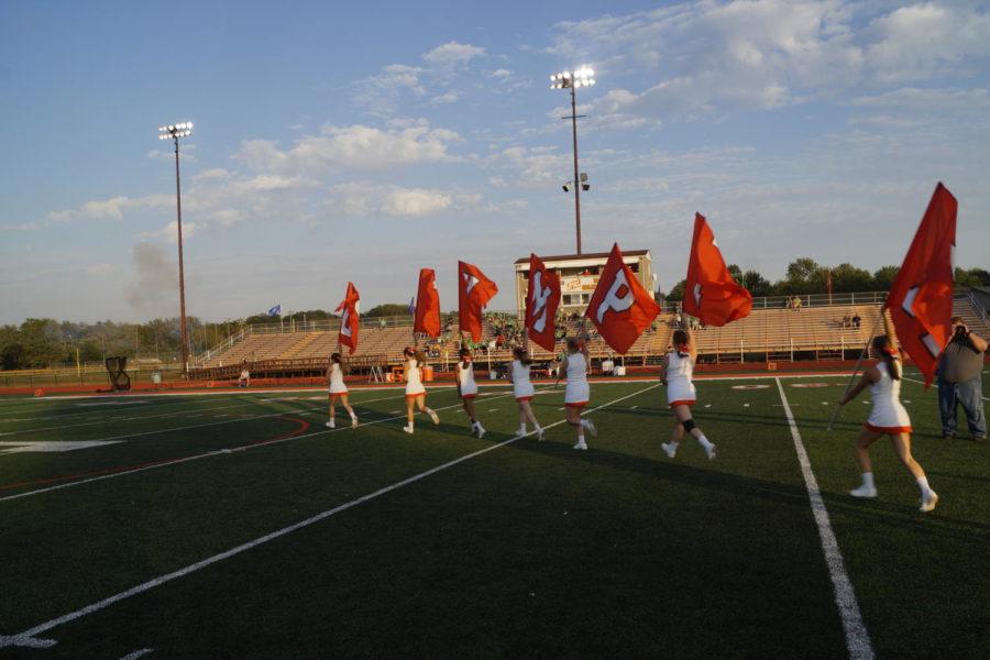 The+varsity+cheerleaders+carry+the+school+spirit+flags+onto+the+field.