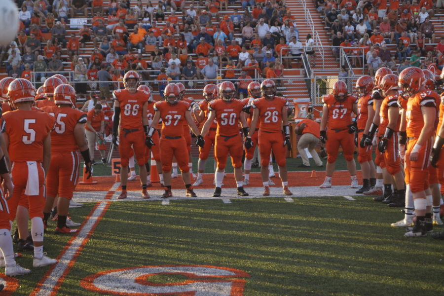 The varsity football players hold hands during the introduction.
