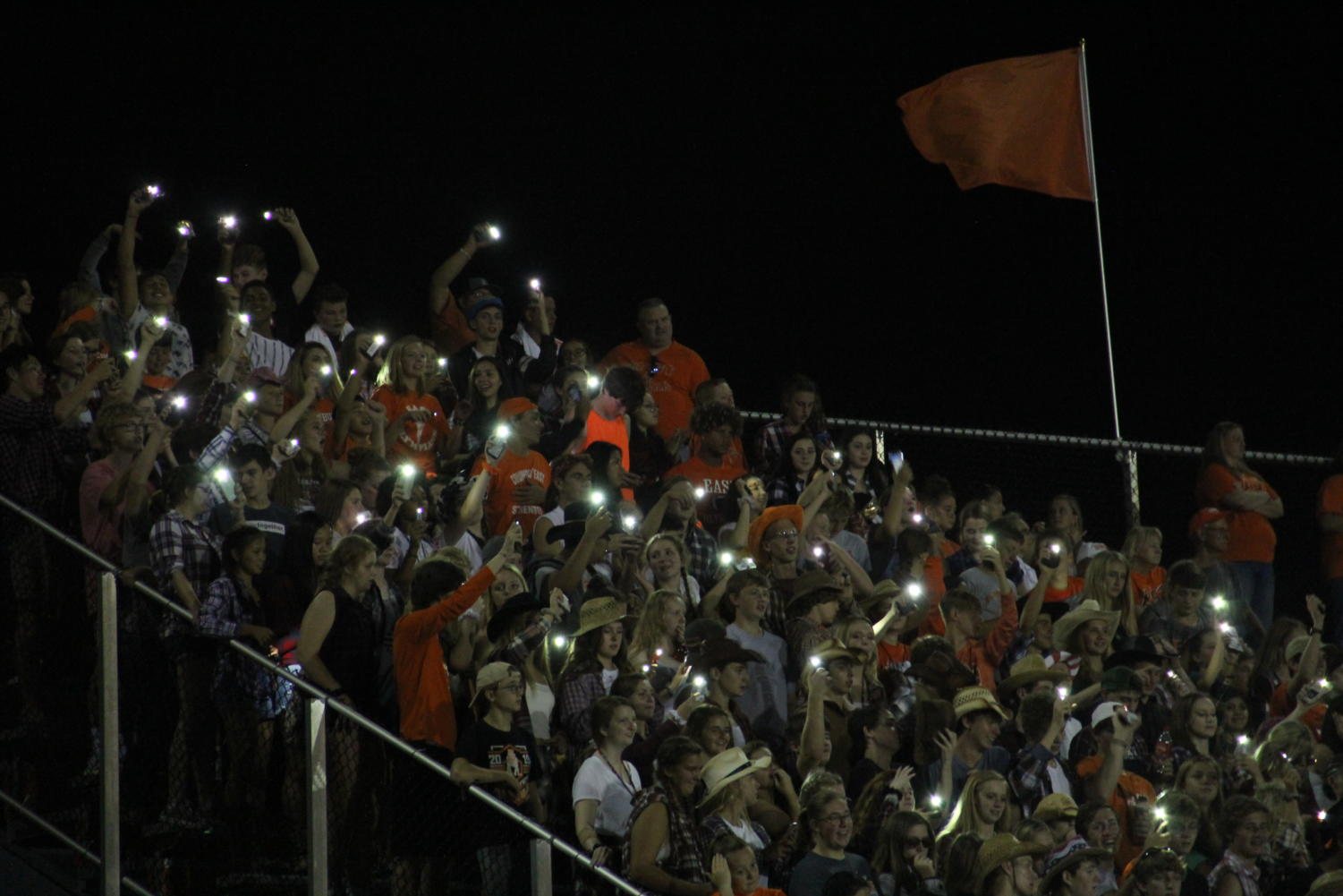 The+student+section+holds+up+lights+from+their+phones.