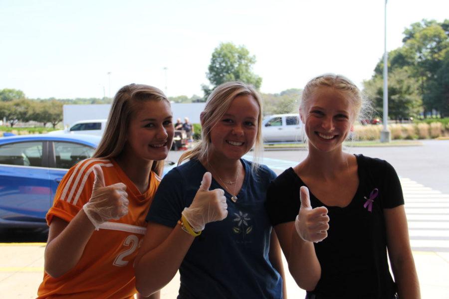 Junior Hannah Hemmerlein, junior Kloe Roberts and junior Marin Wieneke help pass out food at the cookout.