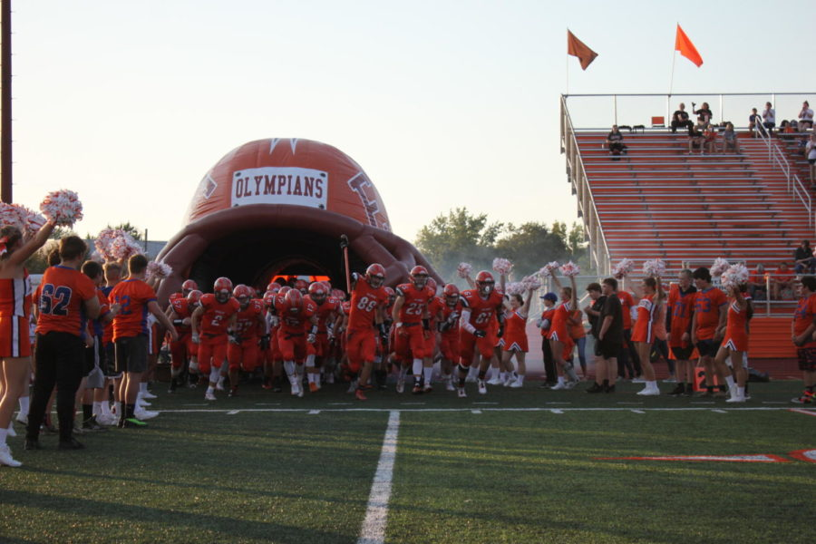 The football players storm onto the field at the start of the game.