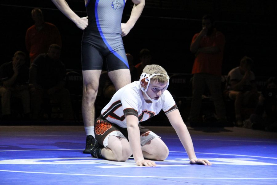 Sophomore Jaden Durnil kneels down in a referee's position.