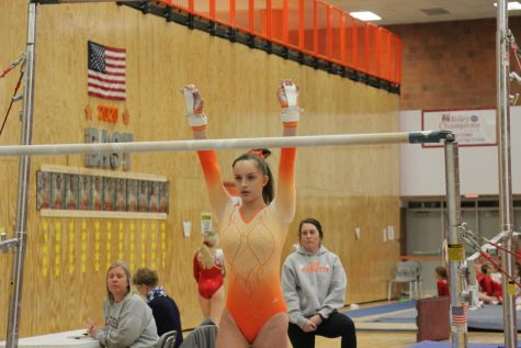 Sophomore Reagan Mount prepares to swing on the low bar.