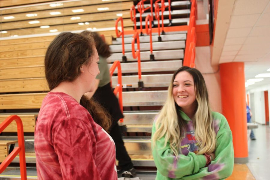 Two students chat while attendance is taken for gym class.