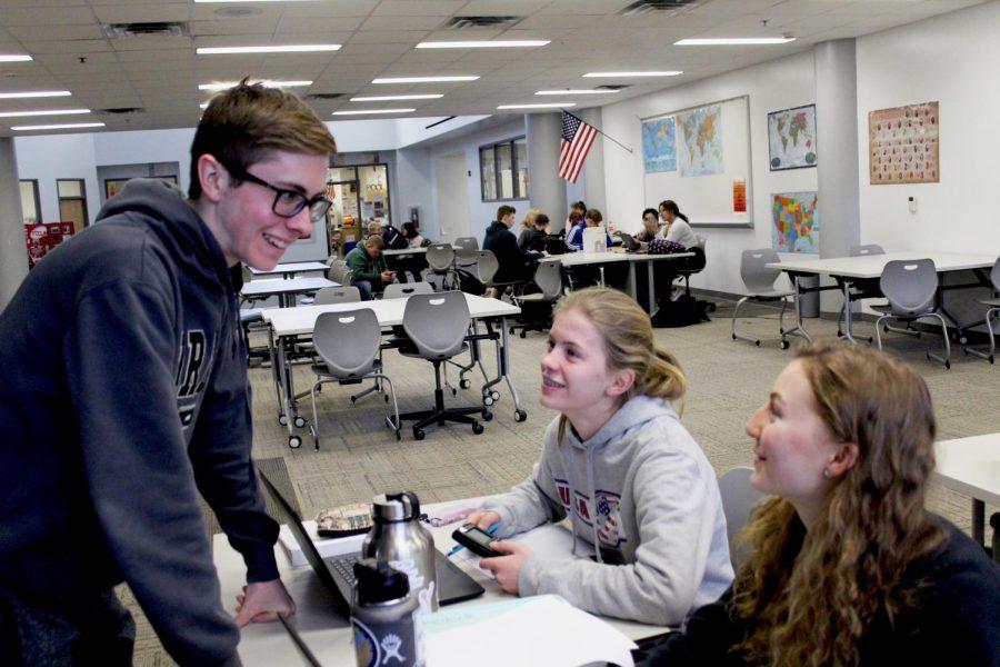 Senior Matthew Novreske checks in on freshman Allison Craig and senior Maya Federle while they finish their schoolwork.