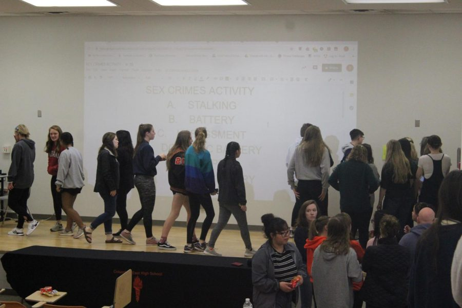 The senior girls walk around the room to identify the different types of abuse described on the wall.