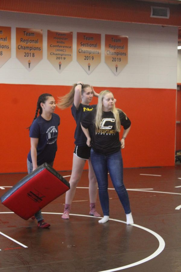 Seniors Faith Briggs, Chesney Loehr and Caitlyn Wager listen to instructions.
