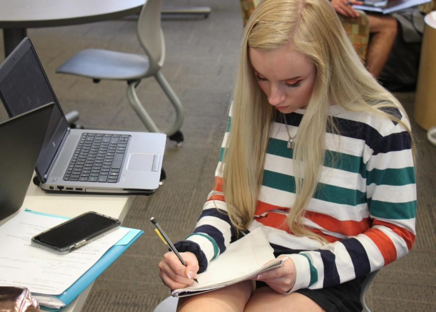 Sophomore Celia Schutte uses the calculator on her phone to finish her math homework.