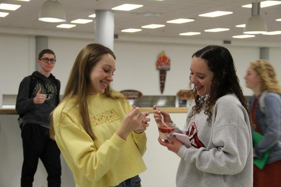 Seniors Anna Emmert and Denesha Megerle laugh together while eating parfaits.
