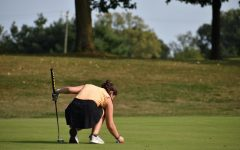 Junior Cristen Martinez marks her ball on the green.