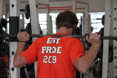 Senior Parker Harrison prepares to squat in weights class.